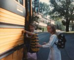 Two young children getting on a school bus in their neighborhood.