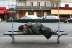 Man sleeping on a street bench.