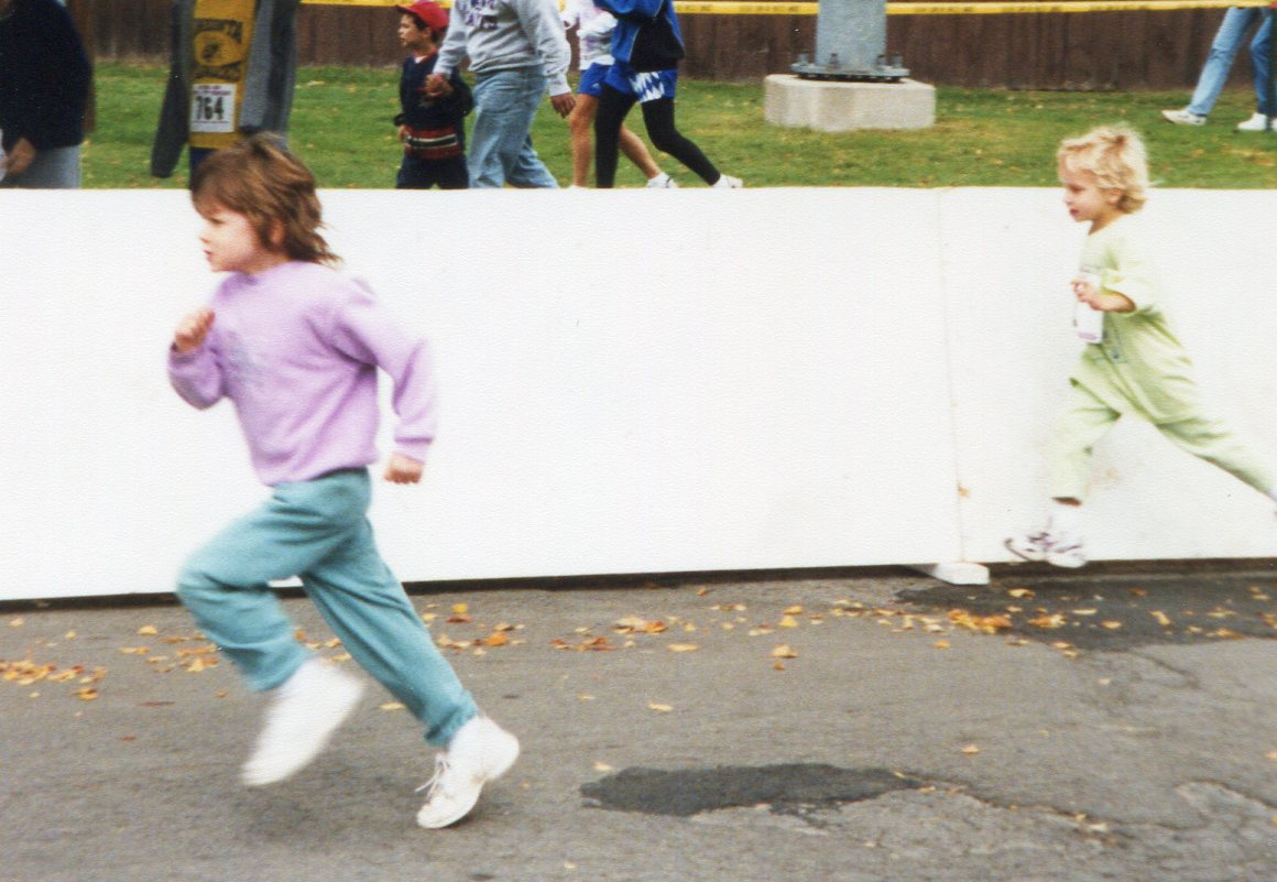 Two young children running a race.