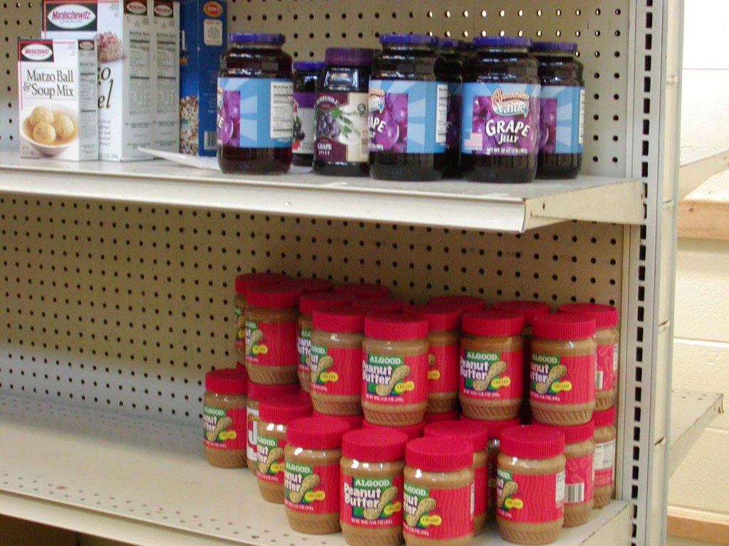 Food bank shelves with just some jars of peanut butte and jelly and empty shelves.