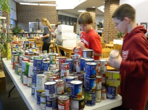Children organizing canned food donations.