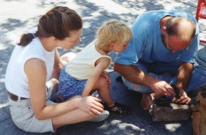 Mother sitting on the ground with child in lap, both watching a craftsman at work who is also sitting on the ground.