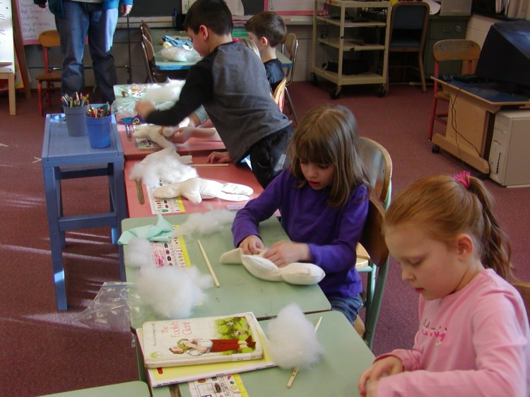 First graders working at their desks to stuff hospital dolls with their fingers.