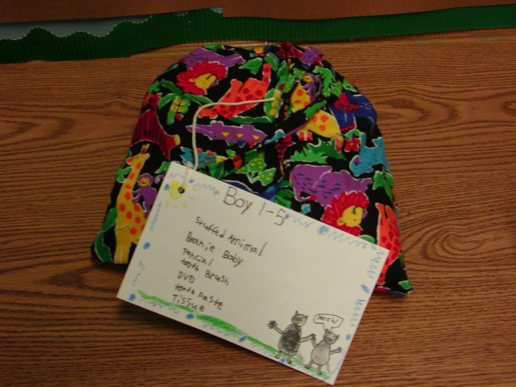 """Colorful cloth bag with a label for """"Boy 1-5"""" and a list of things in the bag: stuffed animal, beanie baby, pencil, toothpaste, toothbrush, DVD, tissues, with colorful drawing around the edges."""