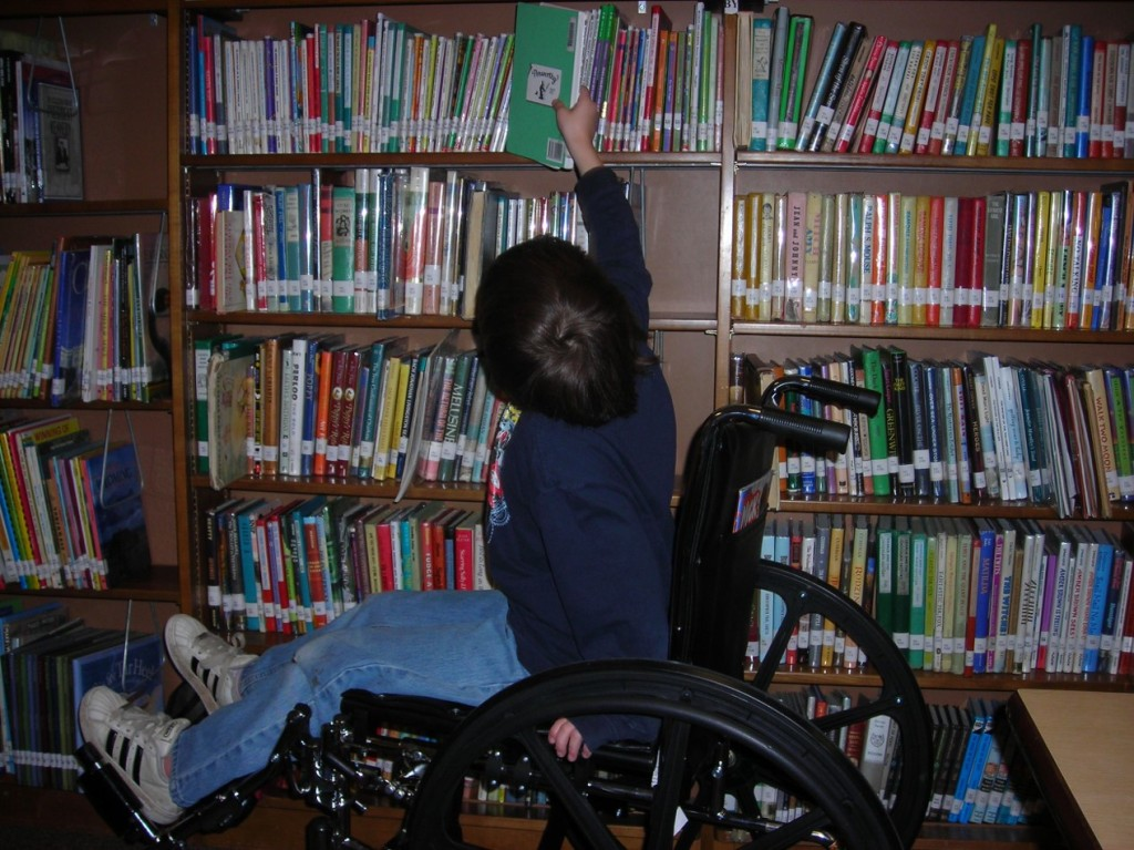 Third grader in a wheel chair reaching to take a book from a library shelf.