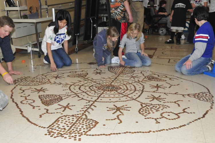 Fourth graders making an Indian design on the floor with donated pennies for their sister city in India.